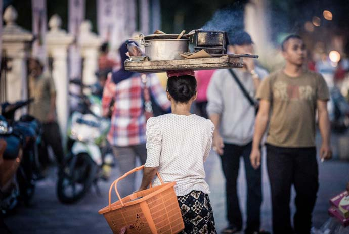 Incredible balancing act. A street vendor balances steaming hot Satay on her head in downtown Kuala Lumpur. Photo by Puguh Indrasetiawan