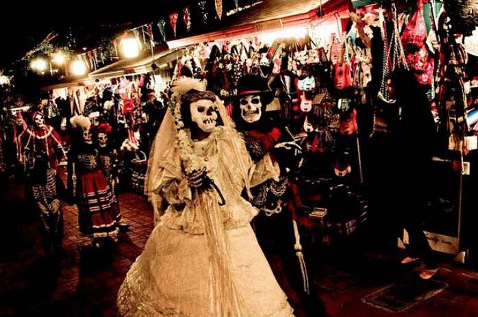 Dressed up couple parade during Dia de los Muertos festival. Photo by Skull Spiration