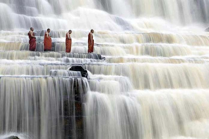 Monks at Pongour Falls in Vietnam. Photo by Lisa Cowgill, Pinterest