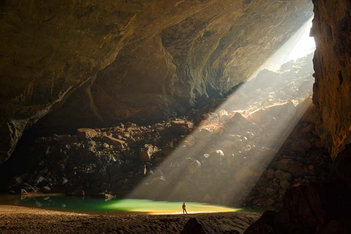 A beam of light shines through onto a tiny person inside the cave. Photo by Ryan Deboodt via Oxalis.com.vn