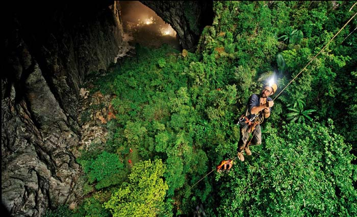 Abseiling through the Son Doong Cave into the dense jungle below. Photo by Liam Nendis, flickr