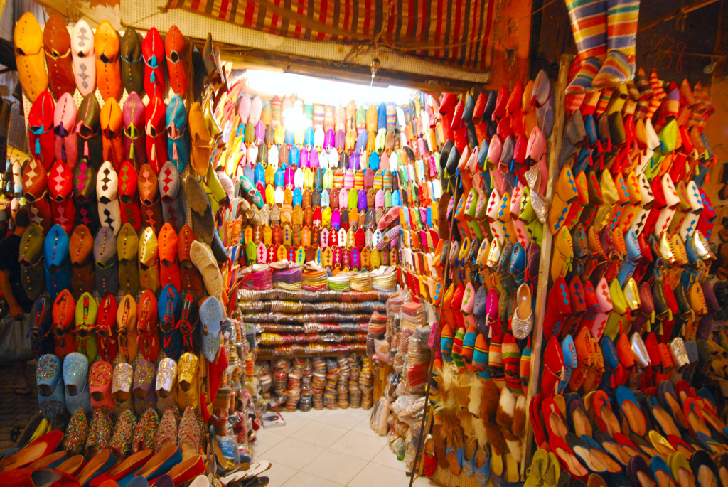 Things to do while staying in Marrakesh: Colourful slippers for sale at the Marrakesh souks. Photo by wikimedia.org