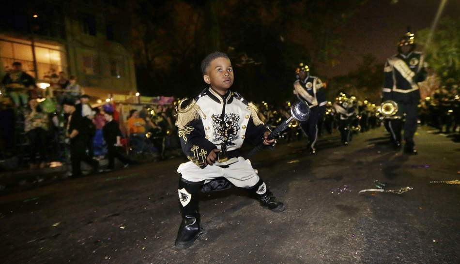 Guide on celebrating Mardi Gras in New Orleans: A 6 year old performs as a drum major with the Roots of Music marching band during the Krewe of Bacchus Mardi Gras parade. Photo by Gerald Herbert