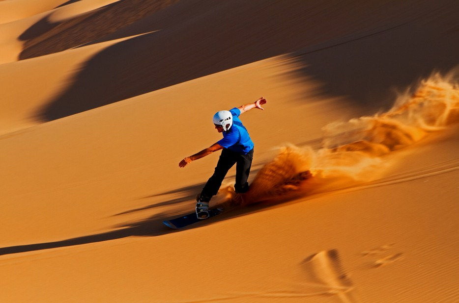 deserts in Namibia: Picking up some serious speed sandboarding. Photo by Klaus Brandstaetter