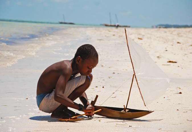 A young boy fixes his wooden sailboat on Jambiani Beach. Photo by Revaz Ardesher, flickr