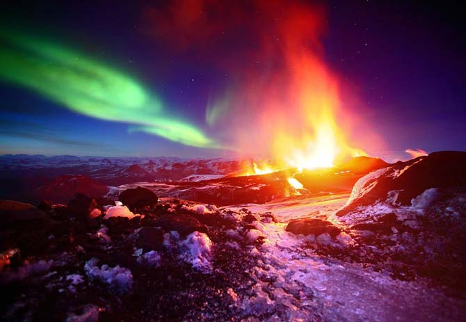 The Fimmvorduhals volcano in Iceland erupts under the Northern lights. Photo by James Appleton