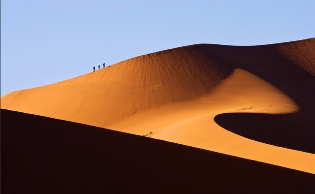 deserts in Namibia: Treking up the side of a dune. Photo by pichost.me
