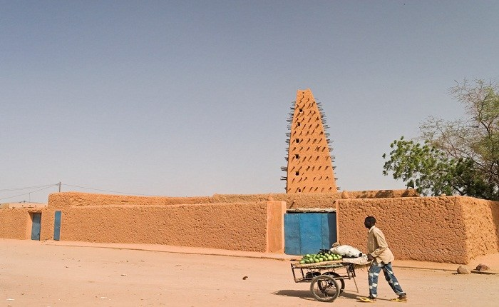 A man pushes a wheelbarrow of watermelong past Agadez Mosque. Photo by Matthew Paulson, Flickr
