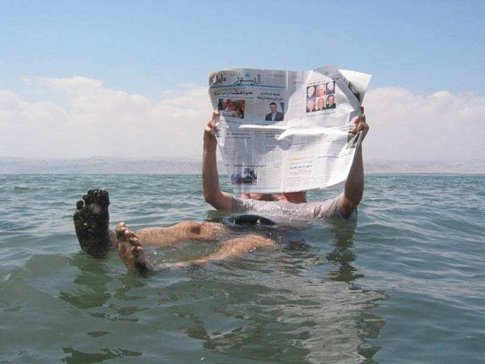 Read a newspaper while floating in the Dead Sea. Photo by wordpress.com