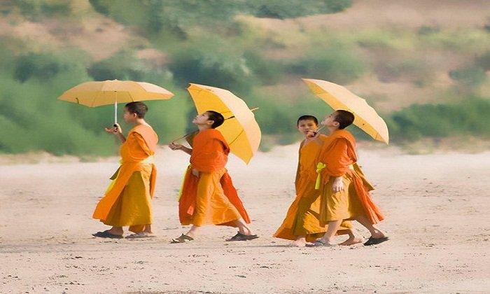 Monks walking along the Mekong River. Photo by simon rackleft via Flickr